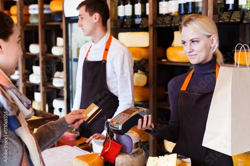 Plakat Klient płaci za zamówienie sera w sklepie spożywczym.