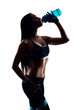 Attractive sporty young woman drinking from blue shaker bottle in studio. Silhouette photo. Isolated on white background.