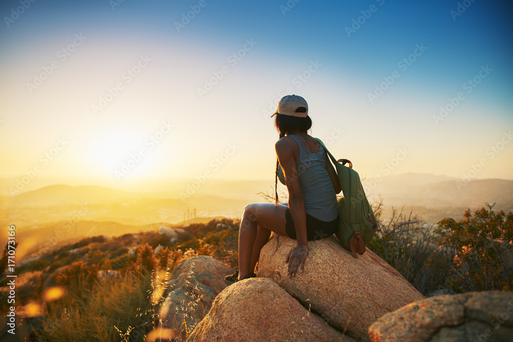 Fototapety, obrazy: Rear view of woman hiker sitting on rock on top of hill while looking at sunset over San Diego California