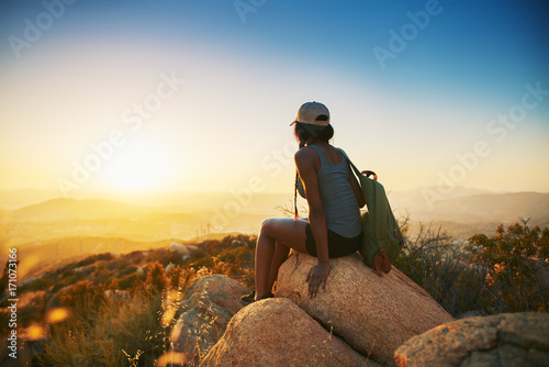 Fototapeta Rear view of woman hiker sitting on rock on top of hill while looking at sunset over San Diego California obraz