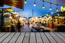 Image Of Wooden Table In Front Of Decorative Outdoor String Lights Bulb In Night Market With Blur People, Festival And Holiday Concepts, Can Used For Display Or Montage Your Products.