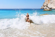 smiling woman getting hit by the big waves at Erimitis beach Paxos Greece