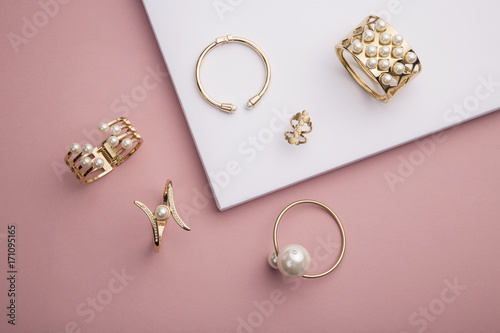 Pearl Golden Bracelets and ring on pink and white background Obraz na płótnie