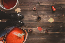 Autumn Background With Copy Space. Woman Holding Cup Of Hot Tea And Pumpkins, Standing On The Wooden Floor