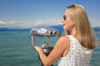 young sexy woman enjoy the beautiful view with a coin operated binoculars. The sun is shining, the water and the sky is blue. she wear sunglasses an a white dress