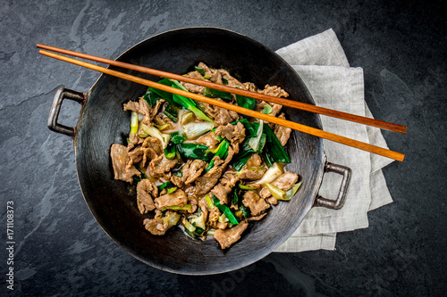 Photo  Traditional chinese mongolian beef stir fry in chinese cast iron wok with cooking chopsticks, stone slate background