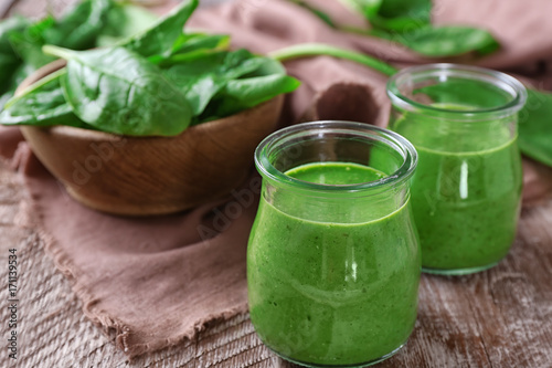 Jars of spinach smoothie on wooden table