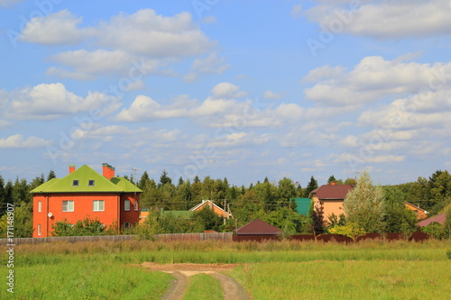 In de dag Groene koraal A picturesque modern Russian landscape: dirt road, bright house against a blue sky with clouds. Concept: suburbs of megacities, closer to nature