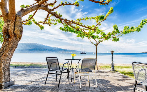 Street outdoor cafe on Embankment of Corinth Gulf beneath the tree Canvas-taulu