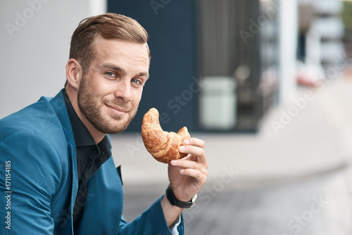 Photo Close up of a cheerful businessman eating croissant