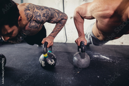 Spoed Foto op Canvas Fitness Gym two man push-up strength pushup exercise with Kettlebell in a workout