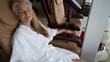 Wearing a white robe, a mature, caucasian woman relaxes back into the thick padding of the pedicure chair at a spa.