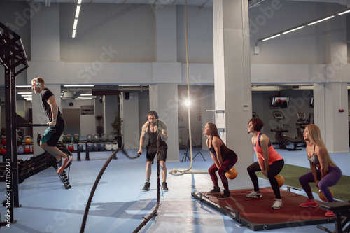 Keuken foto achterwand Ontspanning group of fitness people doing exercise with weights, rope, parallel bars in the gym