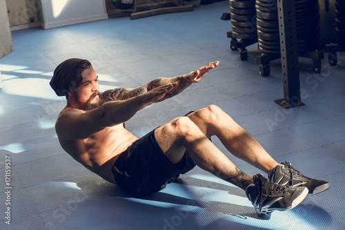 Fotografie, Obraz  Handsome muscular man doing sit-ups on gym floor