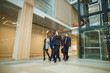 People walk in modern office lobby interior with a meeting room with glass walls