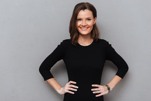 Smiling Woman In Black Dress Posing With Arms On Hips