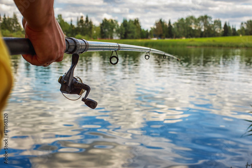 a man with a fishing rod on the river bank is fishing