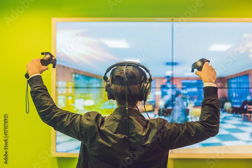 8c63fbc6df7 Young man playing video games virtual reality glasses. Cheerful man having  fun with new trends