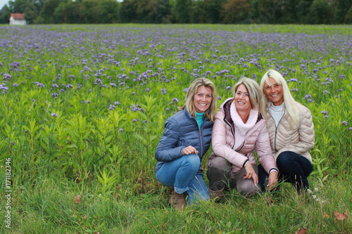 Fotografering  Three happy mature woman sitting in the meadow