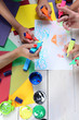 Hands hold colorful markers and draw. Artists wooden table
