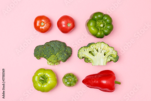 Fotografiet  Top view of broccoli, green pepper, tomatoes, red paprika on a pastel pink background