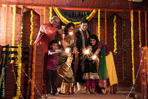 stock photo of Indian Family celebrating Diwali festival with fire crackers with grand parents, young couple and kids in ethnic wear