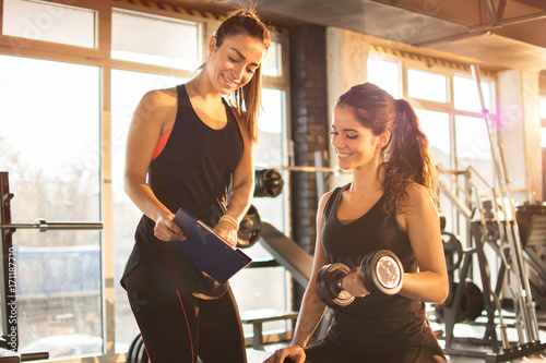 Female fitness instructor showing exercise progress on clipboard to young athletic woman at gym Fototapete