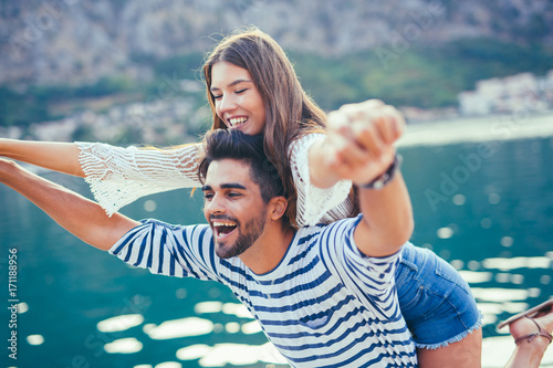 Young beautiful tourist couple enjoying summer holiday on the seaside Poster