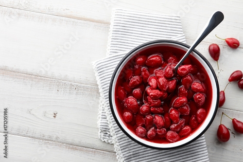 Valokuvatapetti Cornus or dogwood jam with berries on a white wooden background, autumn seasonal