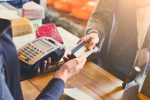 Obraz Customer paying for order of cheese in grocery shop. - fototapety do salonu