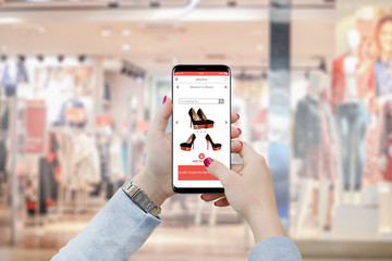 Girl purchasing shoes on her smartphone in front of boutique