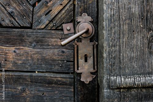 Old Door Handle. Foreground of old wooden door with iron handle..