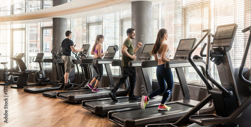 Poster Fitness Group of four people, men and women, running on treadmills in modern and luminous fitness gym