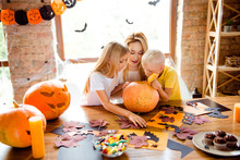 What`s Inside? Blonde Curious Family Of Mommy And Two Siblings Made A Jackolantern, Peeking Inside It, Desktop With Yellow Candles, Treats, Fall Leaves, Little Black Bats On Windows, Garlands