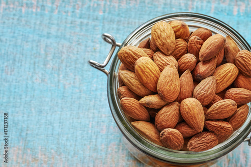 Fotografía  Almonds in a jar on a rustic wooden background, space for text, shallow depth of field