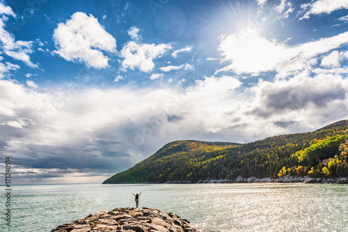 Spoed Foto op Canvas Canada Autumn nature background canadian landscape in Quebec, Canada. Fall season St Lawrence river in Charlevoix region, North America. Tourist with arms up open in freedom happy of travel holidays.