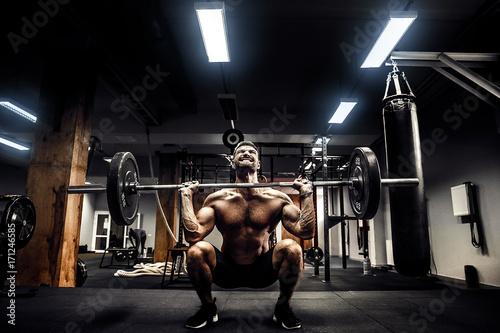 Fényképezés  Muscular fitness man doing deadlift a barbell over his head in modern fitness center