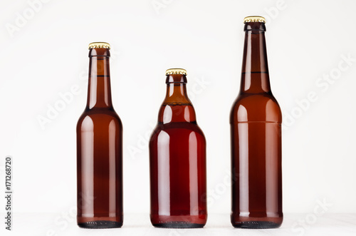 Poster Beer / Cider Set of different brown beer bottles 500ml and 330ml mock up. Template for advertising, design, branding identity on white wood table.