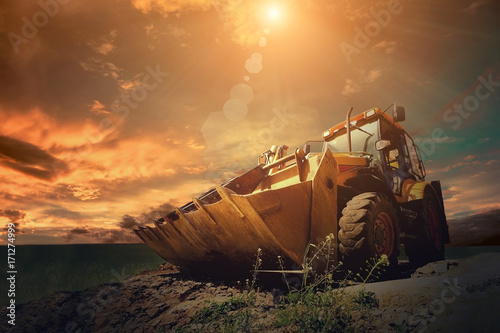 Vászonkép Yellow tractor on sky background