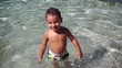 Slow motion - Child smiling looks into camera standing in the sea