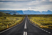 Road No. 1 In Iceland, Asphalt, Mountains And Driving Cars In The Background.