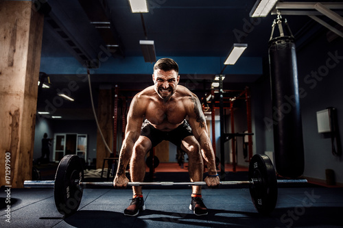 Fényképezés  Muscular strong fitness man doing deadlift of a barbell in modern fitness center