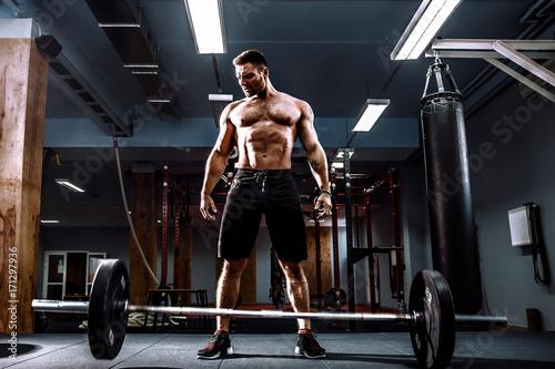 Fényképezés  Muscular fitness man threw the bar on the floor after deadlift of a barbell in modern fitness center