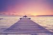 Frau entspannt zum Sonnenuntergang auf einer Bank am See