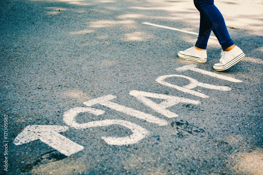 Fototapeta Feet of women with start word on road concept keep going ,hipster tone