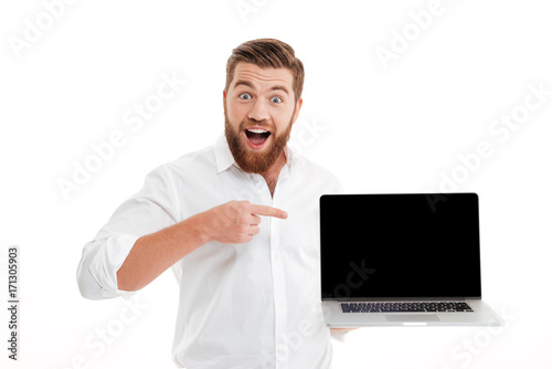 Bearded man standing over white wall showing display of laptop.