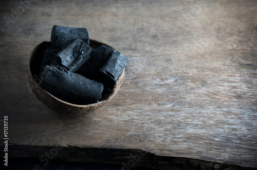 Photo Activated charcoal powder for facial skin carbon in coconut shell for spa on the