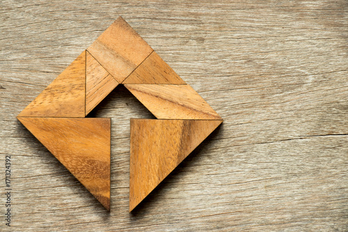 Tangram puzzle in square shape with the arrow symbol inside on wood background Canvas Print