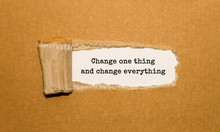 The Text Change One Thing And Change Everything Appearing Behind Torn Brown Paper