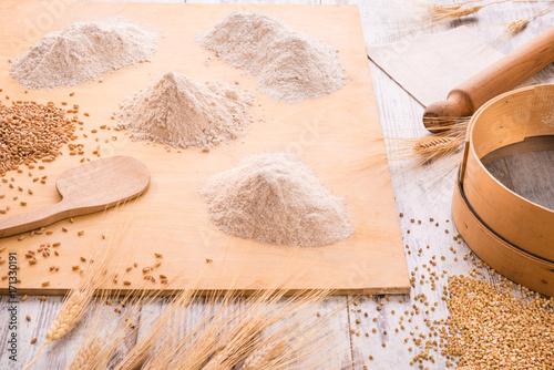 Farine integrali diverse sull'asse di legno con chicchi e spighe, setaccio e mat Tapéta, Fotótapéta